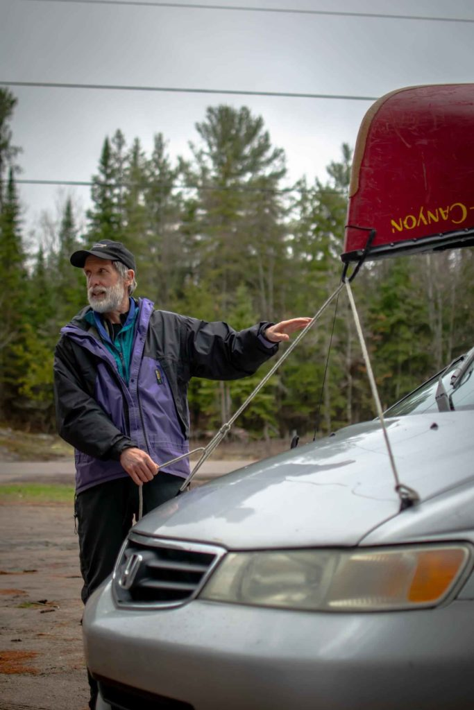 Paul Mason next to car with canoe on its roof