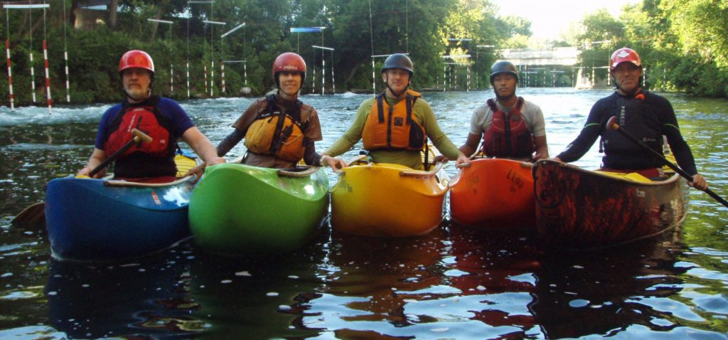 Five canoeists in helmets and life-jackets side-by-side in multi-coloured canoes